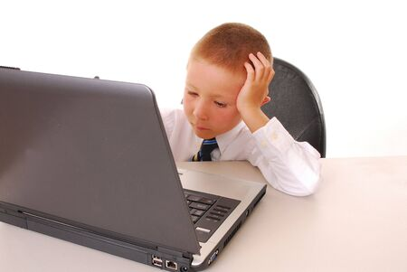Young boy in tie working on computer photo