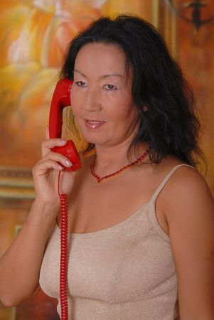 sexy asian woman: Beautiful lady in a warm setting on the phone