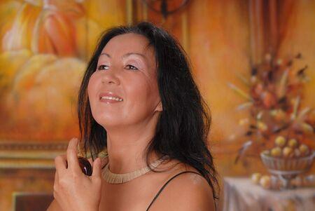 Beautiful lady in a warm setting applying perfume photo