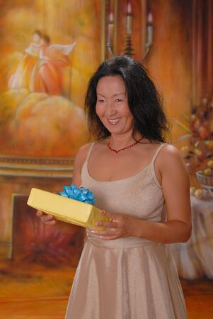 Beautiful lady in a warm setting with a gift photo
