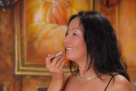 Beautiful lady in a warm setting applying lipstick photo