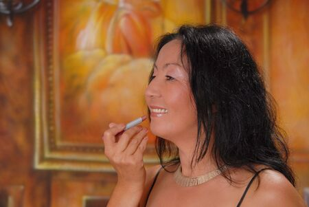 Beautiful lady in a warm setting applying lipstick photo