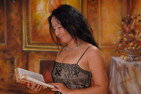 Beautiful lady in a warm setting reading book Stock Photo - 501134
