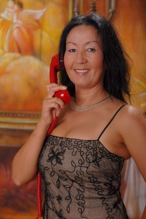 sexy asian woman: Beautiful lady in a warm setting on phone Stock Photo