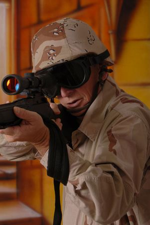 Camouflaged old soldier with sniper rifle inside building Stock Photo - 566246