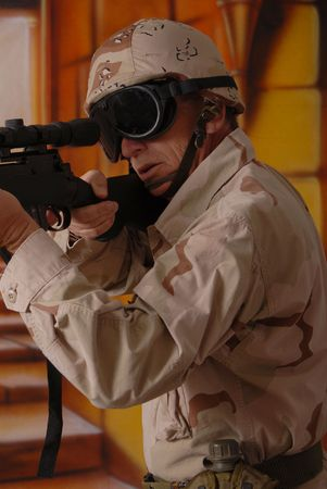 Camouflaged old soldier with sniper rifle inside building Stock Photo - 566259