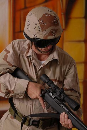 Camouflaged old soldier with sniper rifle inside building Stock Photo