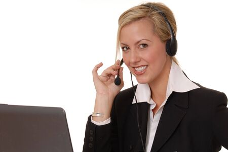 Beautiful and sexy blond business woman with headset and laptop Imagens