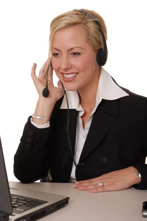 Beautiful and sexy blond business woman with headset and laptop photo