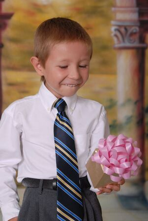 Young boy in tie with wrapped gift