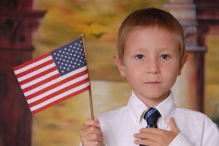 Young boy in tie holding American flag Imagens
