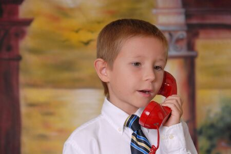 Young boy in tie listening on standard phone