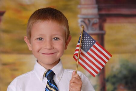 Young boy in tie holding American flag Stock Photo