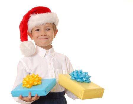 handsom: Muchacho joven del handsom que usa un sombrero de Pap� Noel y que sostiene los regalos Foto de archivo