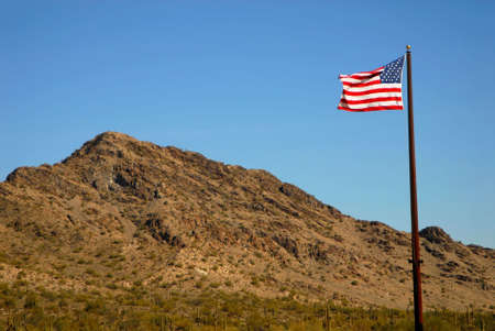 Dramatic desert mountains with an American flag flying