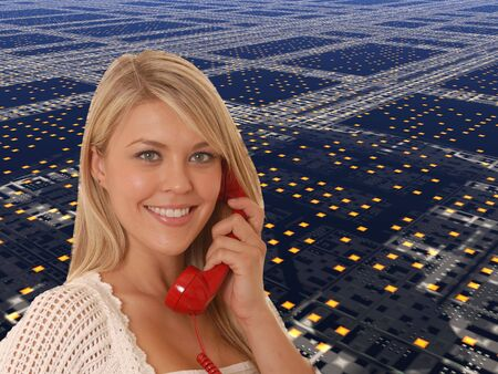 Lovely blond business woman talking on a standard telephone in front of a high tech background Stock Photo