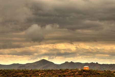 Dramatic desert mountains with a storm approaching and water storage tank