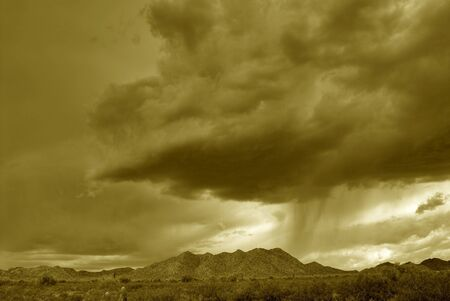 Sepia tone of Dramatic desert mountains with a storm approaching Banco de Imagens