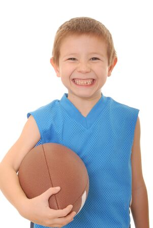 Young boy playing with an American style football isolated Imagens