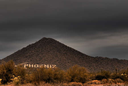 tuscon: Large sign on a desert mountain pointing the direction to Phoenix