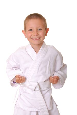 Young boy dressed wearing a karate outfit Imagens