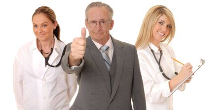 Senior doctor physician isolated on white with his medical team photo