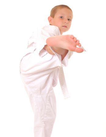 Young boy practicing karate isolated on white Imagens