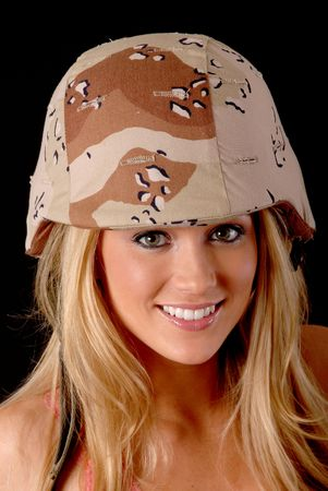 Isolated lovely and sexy young blond girl wearing an army helmet photo