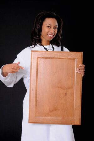 Lovely young and beautiful african american Doctor or Nurse holding a blank wooden sign Stock Photo - 3026002