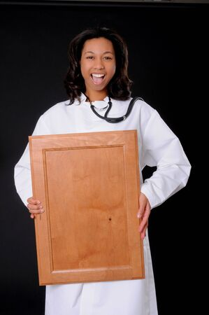 Lovely young and beautiful african american Doctor or Nurse holding a blank wooden sign Stock Photo - 3025908