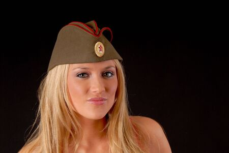 Isolated lovely and sexy young blond girl wearing a soviet army cap photo