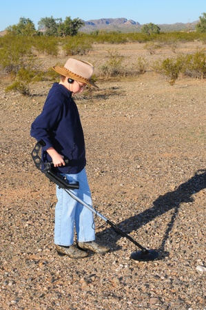 metal detector: Young boy hunting for treasure with a metal detector
