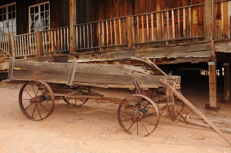 wagon wheel: Old broken down wooden wagon in a ghost town