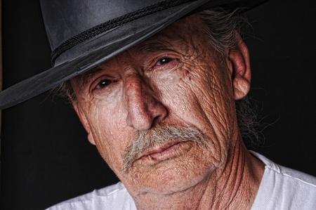 Portret van een oude cowboy met een tandenstoker in zijn mond