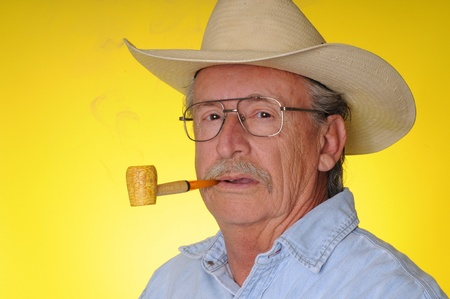 Old senior cowboy smoking a corncob pipe  photo