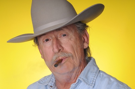 Portrait of on old senior cowboy smoking a cigar photo
