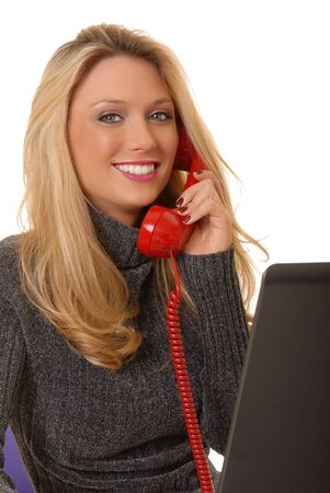 Lovely blond business woman working at laptop computer and talking on standard telephone