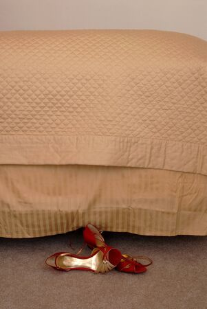 bedspread: One pair of ladies shoes at bedside