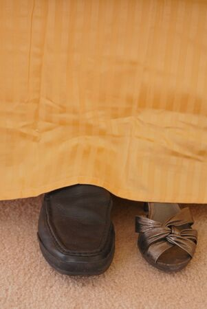 bedspread: One ladies shoe at bedside and one mans shoe