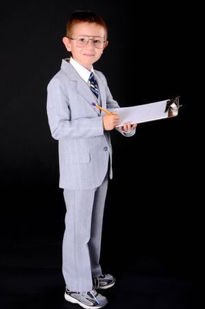 Young boy dressed formally wearing a suit taking notes on a clipboard Imagens