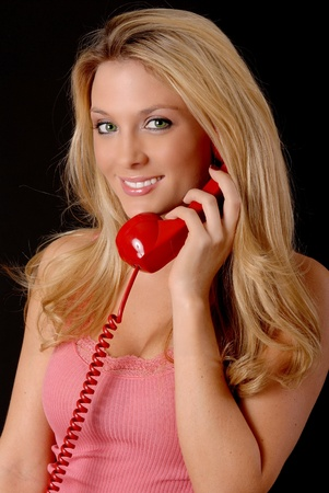 Isolated lovely and sexy young blond girl talking on a telephone photo