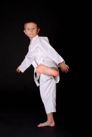 Young boy in karate outfit making fighting movement Imagens