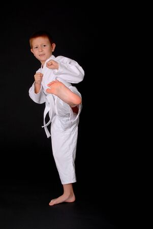 Young boy in karate outfit making fighting movement photo