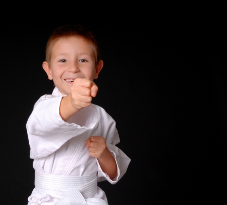 asian art: Young boy in karate outfit making fighting movement Stock Photo
