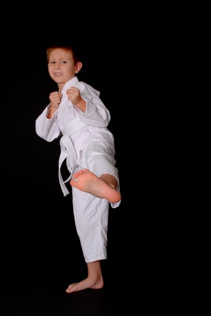 Young boy in karate outfit making fighting movement Фото со стока