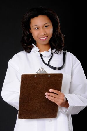 Lovely young and beautiful african american Doctor or Nurse writing on a clipboard Imagens