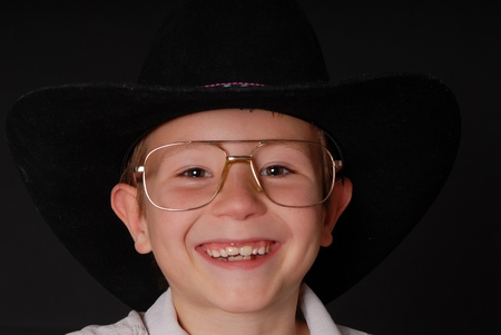Young boy wearing a cowboy hat isolated on black Stock Photo - 9016270