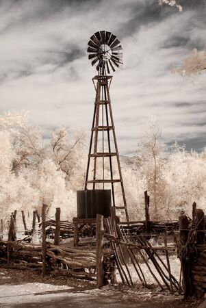 Windmill and water storage tank by a desert corral Banco de Imagens