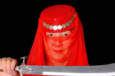 Beautiful arabian style dancer with red veil and sword photo