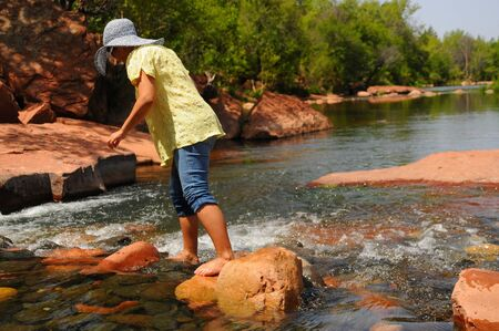 Woman crossing a river barefooted photo